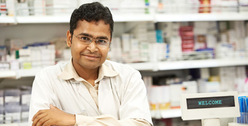 Pharmacist stood in front of medication shelves